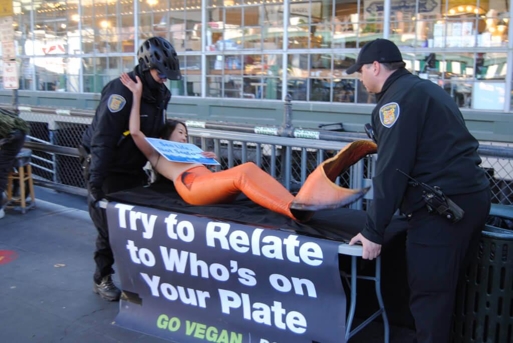 Police Carrying Mermaid Protestor