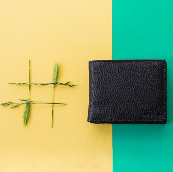 photo of black vegan wallet against a peach and blue backdrop