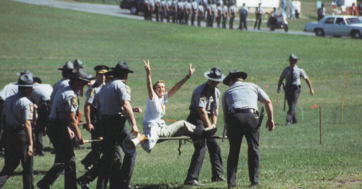 Ingrid E. Newkirk Being Hauled Away From a Demo by Police Officers