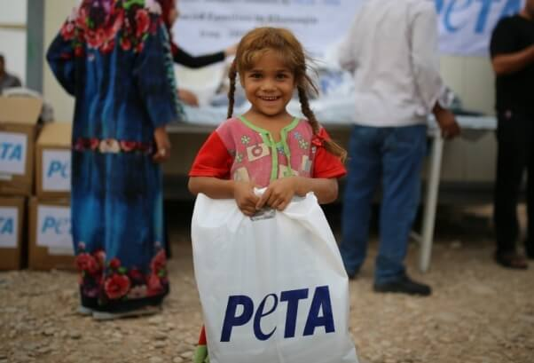 Little girl with PETA bag at refugee camp in Iraq