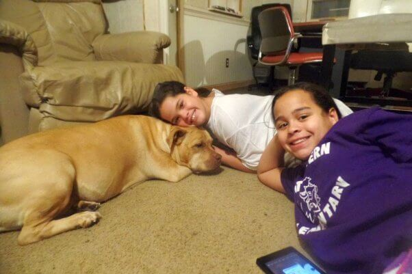 dog and two girls smiling
