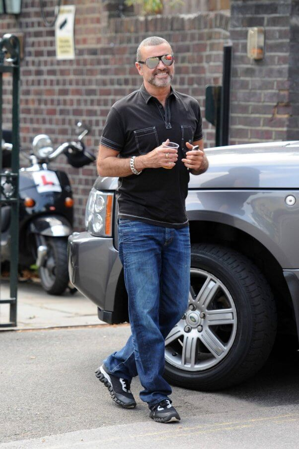 George Michael seen with an ice cool beverage as he arrives at a studio on a hot summer's day in London.