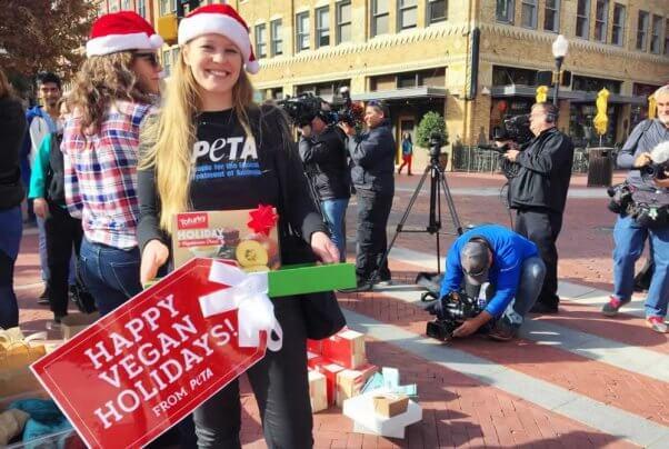 PETA supporter in Santa hat in front of press representatives