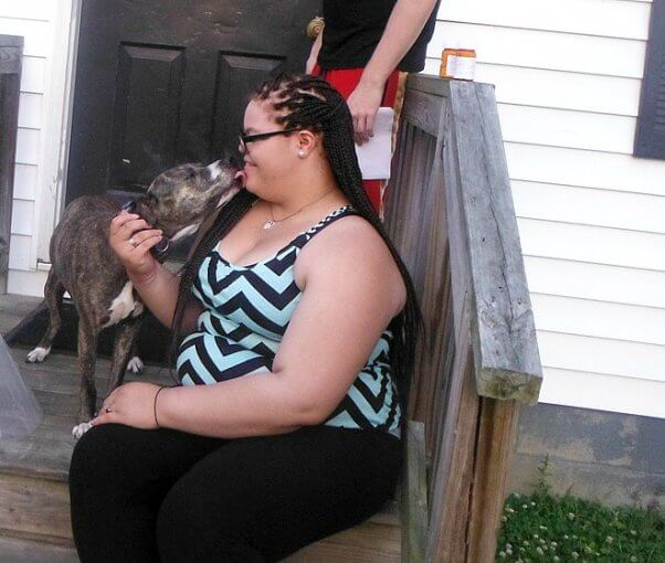 Dog kissing woman sitting on staircase