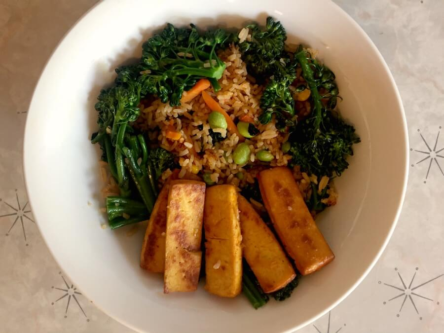 Bowl of vegetable fried rice with broccoli and baked tofu