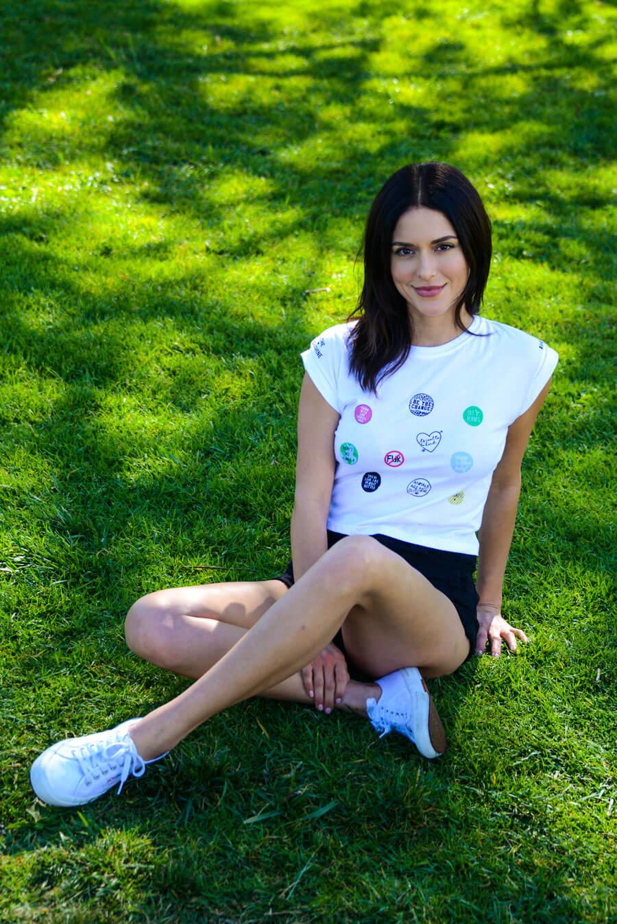 PETA model on grass wearing collab tee