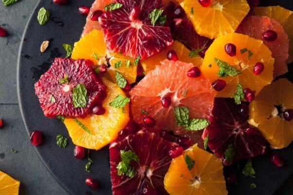 Colorful citrus fruit salad on black plate