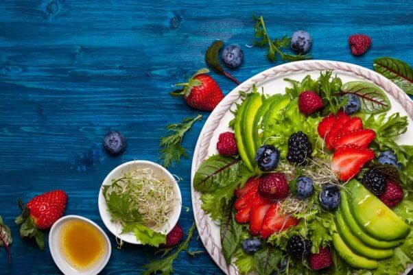 Salad with berries and avocados laid out on blue tabletop