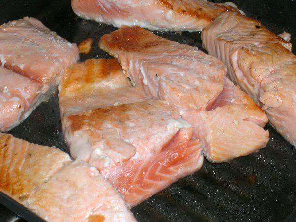 Salmon flesh baking on sheet with oozing white goo