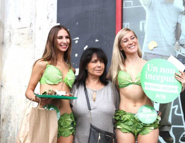 a woman poses in between two Lettuce Ladies in Bucharest