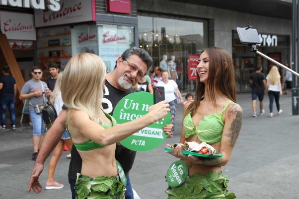 a man takes a selfie with a Lettuce Lady in Romania