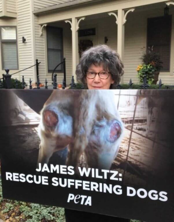 """Woman holding sign reading """"James Wiltz: Rescue Suffering Dogs"""""""