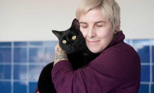 Pretty black cat being snuggled by PETA fieldworker