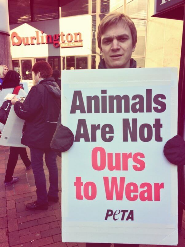 """A PETA staffer holds a sign reading """"Animals Are Not Ours to Wear"""" outside Burlington Coat Factory"""