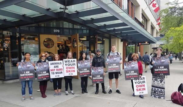 PETA supporters holding signs about the cruelty of down standing outside lululemon shareholder's meeting.