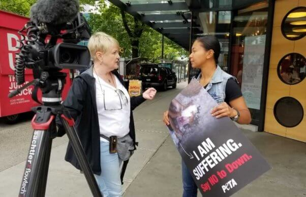 PETA supporter holding anti-down side talks with press outside lululemon shareholder meeting