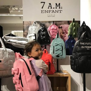 young girl standing in front of a vegan backpack display