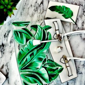white and clear bag painted in green tropical leaves