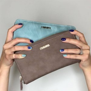 two hands hold vegan leather clutches in gray and light blue