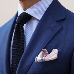 person in blue suit and vegan knit tie