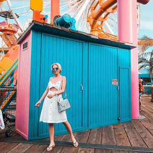 woman in white stands in front of a blue and pink panted building at a carnival
