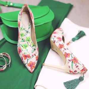 floral patterned high-heeled shoes on a green and white background