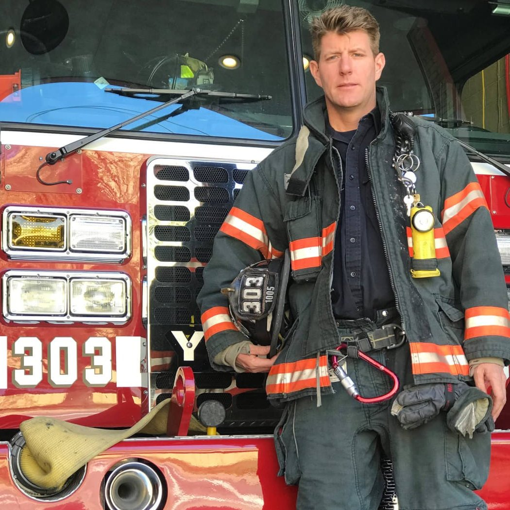 a man in a firefighters uniform stands in front of a fire truck