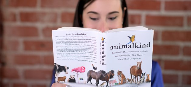 woman reads animalkind by ingrid newkirk against a brick wall
