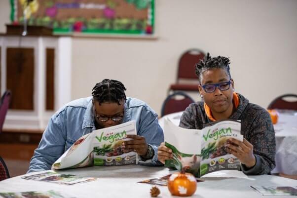 People Reading Vegan Starter Kits at Vegan Thanksgiving Event