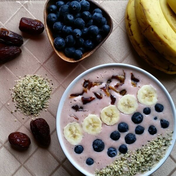 strawberry smoothie bowl topped with blueberries, banana, seeds, dates