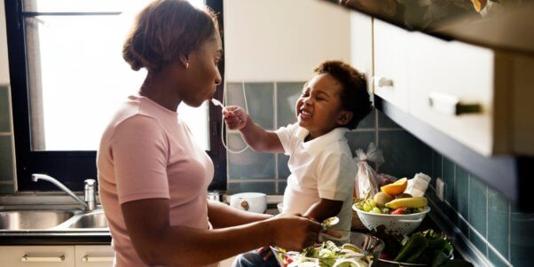 Baby feeding mother who is preparing vegetables