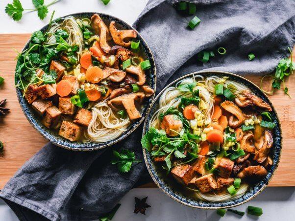Vegan noodle bowl with tofu, mushrooms, onion, carrot