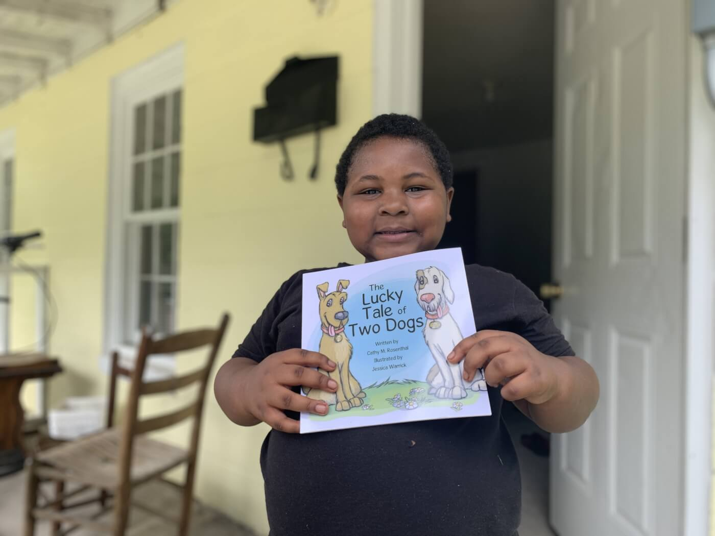 Young child holding a children's book and smiling