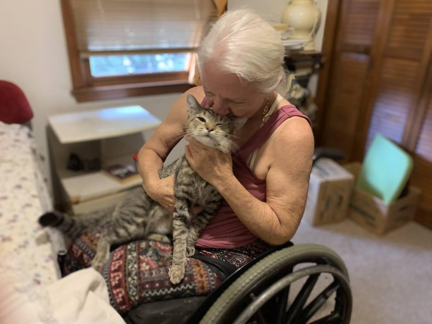 A woman in a wheelchair cuddling a grey cat