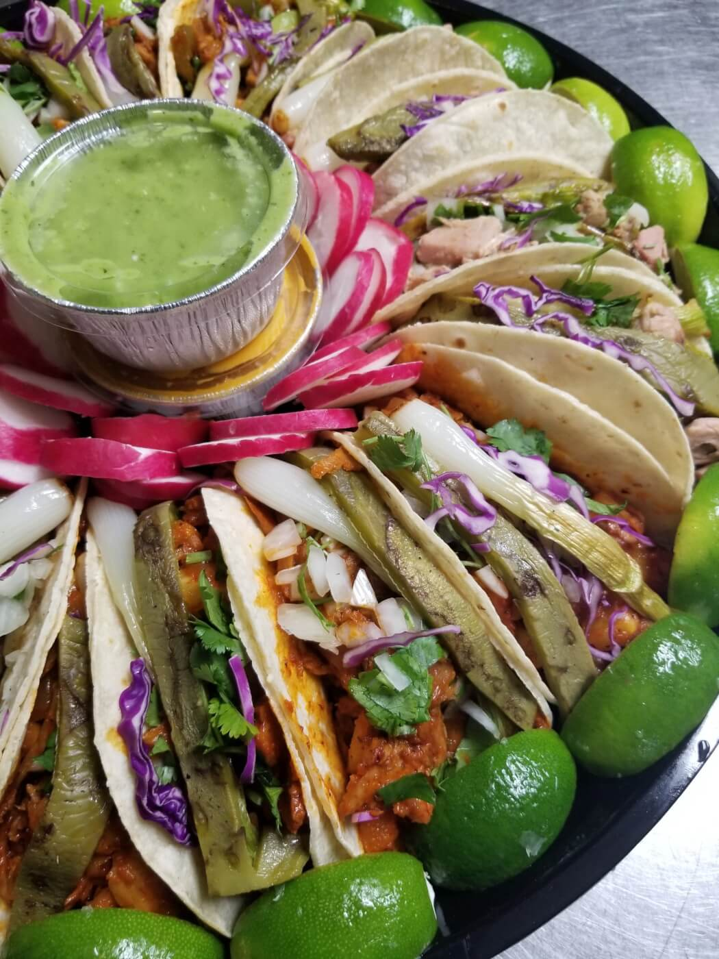 tacos on a plate with a green sauce