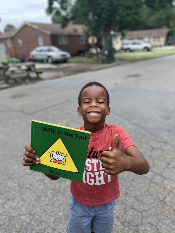 A kid smiles with an animal-friendly book from PETA fieldworkers