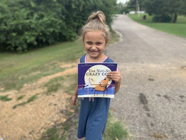 Kid with animal-friendly book from PETA's fieldworkers