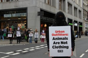 protestors stand outside urban outfitters in London with signs
