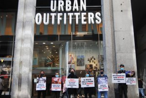 Protestors in Milan standing outside an Urban Outfitters store with posters depicting animals in pain