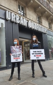 Protestors in Paris stand outside of Urban Outfitters with signs