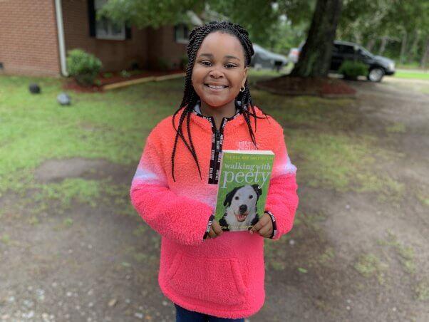 Holding Book from PETA's Barks to Books Program