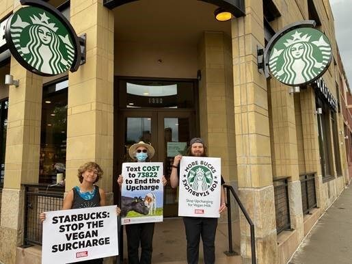 3 protestors stand outside of a Starbucks