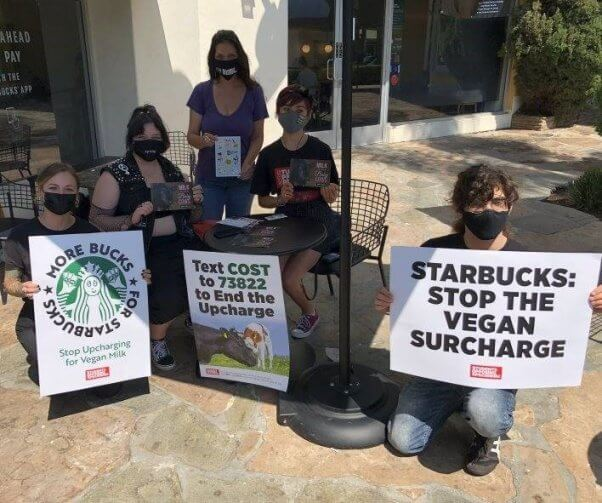 A group of PETA supporters pose for a photo with their signs outside of a Starbucks store